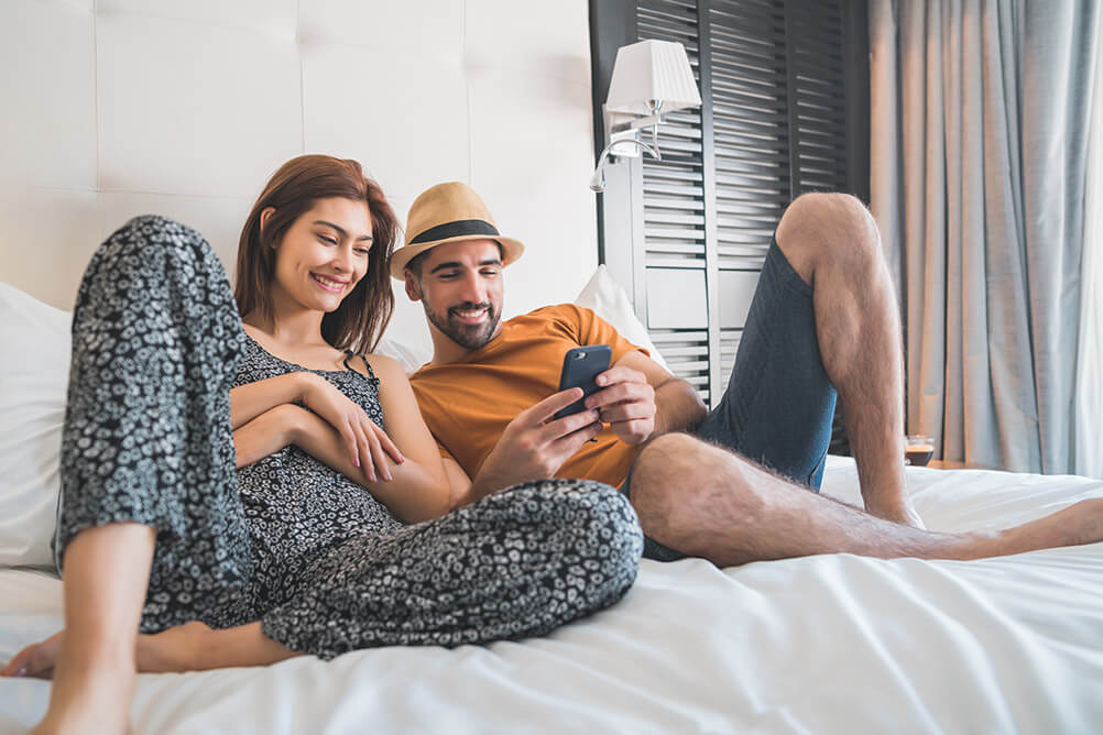 A couple uses a smartphone app in their hotel